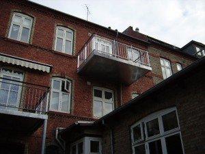 """994. Små altaner på byhus - Værn / gelænder: lodrette balustre med """"luft"""" foroven og håndliste i træ"""